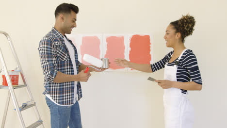 Laughing-young-couple-choosing-a-paint-color