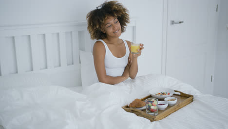 Content-woman-enjoying-breakfast-in-bed