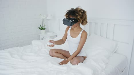 Content-woman-in-VR-glasses-on-bed