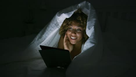Woman-using-tablet-under-blanket