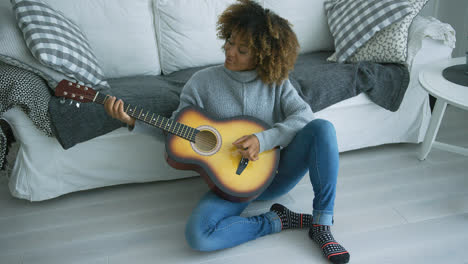 Young-woman-playing-guitar-at-home