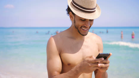 Smiling-man-texting-with-smartphone