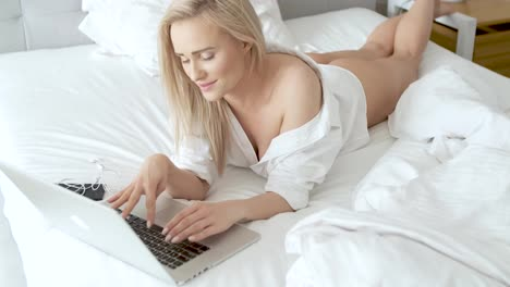 A-smiling-blonde-woman-lying-down-the-bed-in-front-of-her-laptop