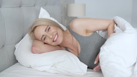 Smiling-casual-blonde-lying-in-her-bed-in-bright-bedroom