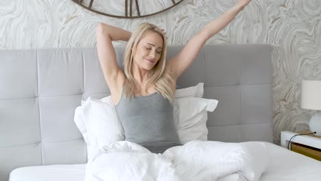 Happy-young-woman-enjoying-sunny-morning-on-the-bed