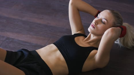 Sporty-woman-doing-abdominal-crunches-on-floor