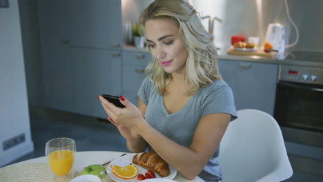Smiling-woman-browsing-smartphone-during-breakfast
