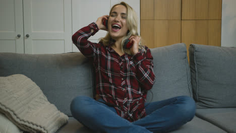 Woman-in-headphone-having-fun-on-sofa