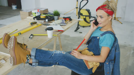 Female-carpenter-at-workplace-talking-on-smartphone-