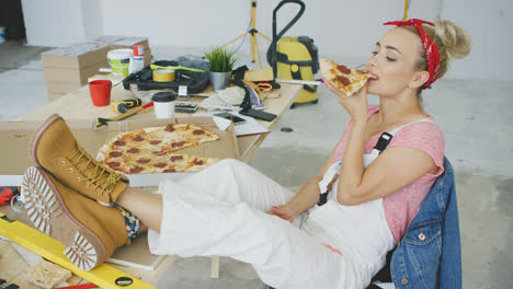 Female-carpenter-eating-pizza-at-workplace