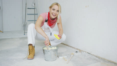 Smiling-female-mixing-yellow-wall-paint-