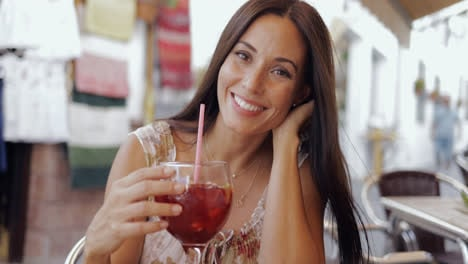 Smiling-woman-posing-with-drink-in-cafe