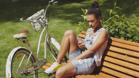Youngster-with-smartphone-and-bicycle