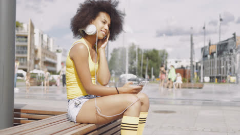 Model-in-headphones-sitting-on-bench