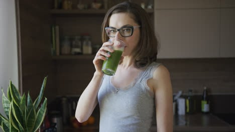 Young-woman-drinking-smoothie-at-home