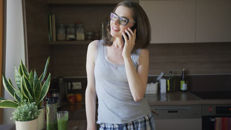 Attractive-woman-talking-on-smartphone-standing-in-kitchen
