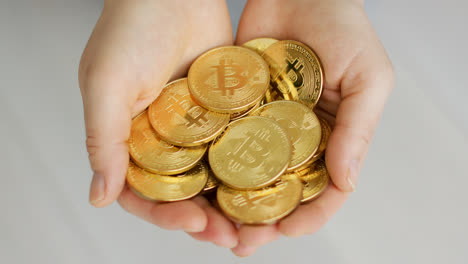 Hands-with-pile-of-golden-coins