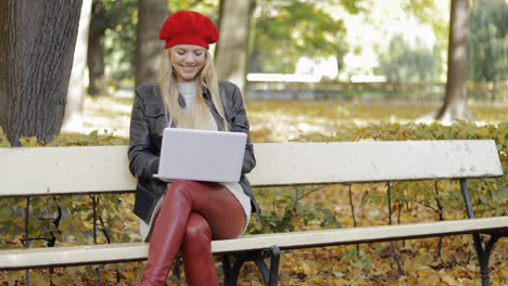 Smiling-woman-using-laptop-in-park