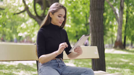 Smiling-beautiful-woman-sitting-on-bench-in-green-park-and-using-tablet