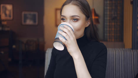 Gentle-young-woman-holding-carefully-cup-of-coffee-and-drinking