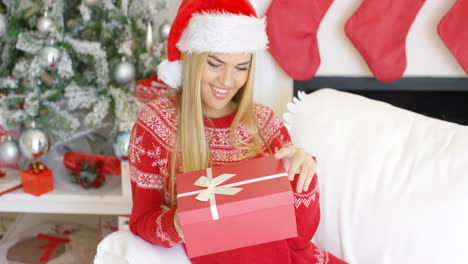 Pretty-smiling-blondie-looking-at-her-boxed-christmas-gift