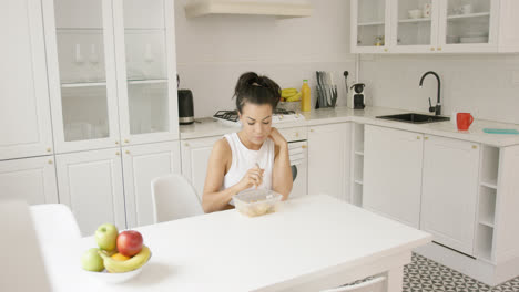 Young-female-eating-in-kitchen-alone