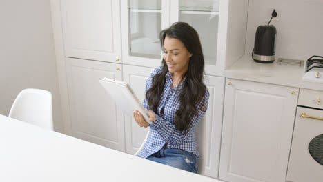 Smiling-woman-with-tablet-in-kitchen