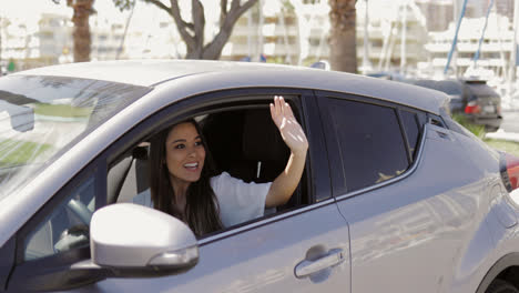 Cheerful-woman-waving-out-of-car