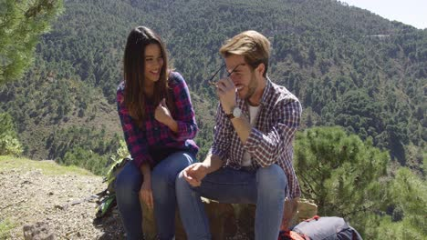 Young-couple-resting-on-stone-in-mountains