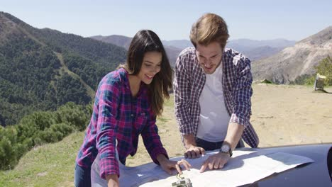 Couple-investigating-map-during-mountain-trip
