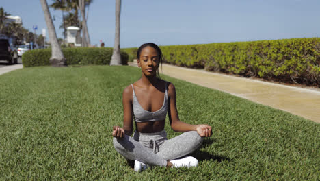 Woman-relaxing-and-meditating-on-lawn