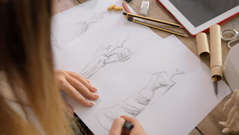 Crop-shot-of-dressmaker-drawing-sketches