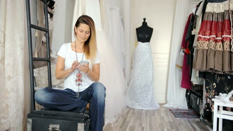 Woman-in-tailor-s-shop-with-phone