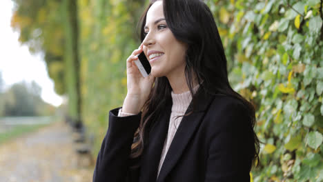 Smiling-woman-speaking-on-phone-in-park