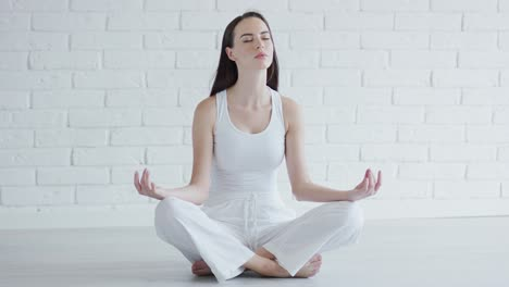 Young-woman-meditating-in-white-room