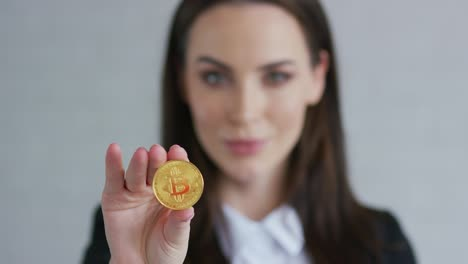 Pretty-young-woman-in-black-jacket-demonstrating-bitcoin-and-looking-at-camera