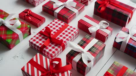 Side-view-of-wrapped-Christmas-presents-laid-on-the-wooden-table