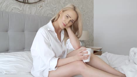 Beautiful-blond-woman-drinking-a-coffee-while-sitting-on-her-bed-at-home