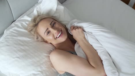 Smiling-blonde-woman-lying-in-her-bed-in-bright-bedroom-under-quilt-