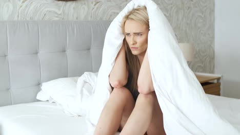 Depressed-young-model-posing-on-cozy-bed-wrapped-in-warm-blanket