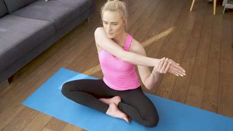 Attractive-young-blonde-woman-exercising-and-sitting-in-yoga-lotus-position
