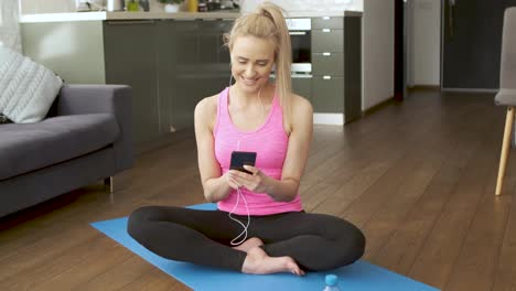 Cute-woman-sitting-on-yoga-mat-and-browsing-mobile-phone-for-songs