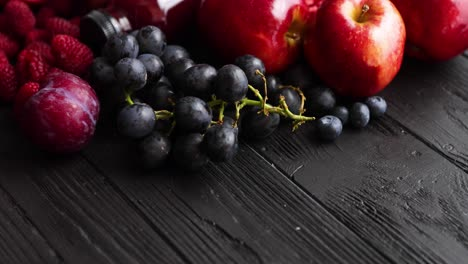 Various-fresh-red-purple-black-fruits-Mix-of-fruits-and-bottled-juices-on-black