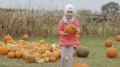 Girl-posing-with-bright-pumpkin-in-yard