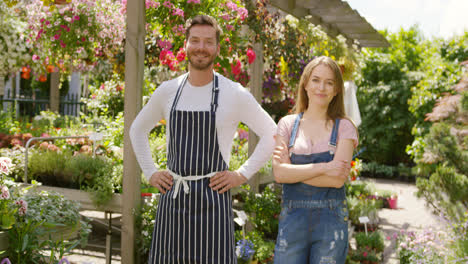 Outdoors-shot-of-cheerful-male-and-female-gardeners-looking-at-camera