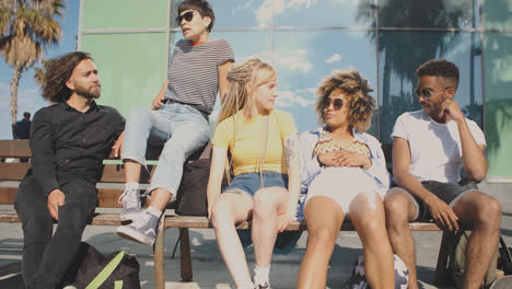 Cheerful-modern-friends-on-bench-in-summertime