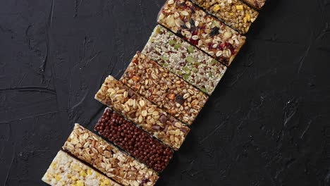 Various-healthy-granola-bars-placed-in-a-row-on-black-stone-table