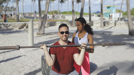 Girl-training-man-in-beach-gym
