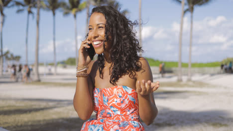 Cheerful-woman-speaking-on-phone-outside