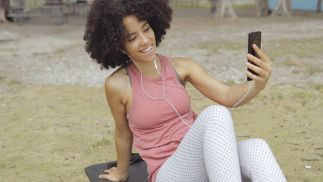 Charming-girl-having-videocall-on-mat-in-park